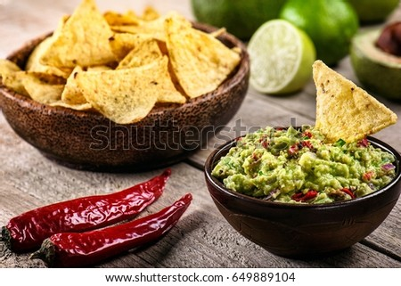 Bowl of guacamole with nachos, chili, and lime on an old wooden background #649889104