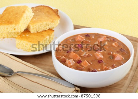 Bowl of ham and bean soup with corn bread on the side