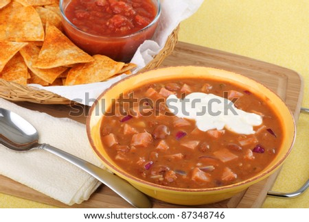 Bowl of ham and bean soup with sour cream and tortilla chips and salsa in background