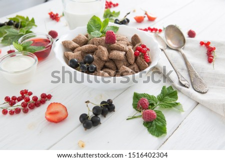 Bowl of healthy corn flakes breakfast cereal topped with fresh blackcurrants and strawberries served in a white ceramic bowl for a delicious meal Healthy tasty breakfast chocolate square pads #1516402304