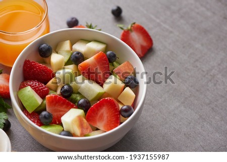Bowl of healthy fresh fruit salad. fresh fruit and vegetable salad, healthy breakfast. bowl of oat granola with yogurt. Orange juice drink.