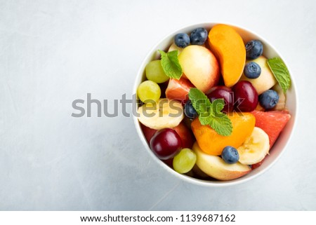 Bowl of healthy fresh fruit salad on a white background. Top view with copy space. Flat lay Stock photo ©
