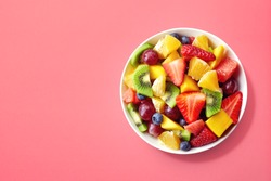 Bowl of healthy fresh fruit salad on pink background, top view