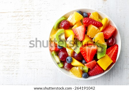 Bowl of healthy fresh fruit salad on wooden background. Top view. #264191042
