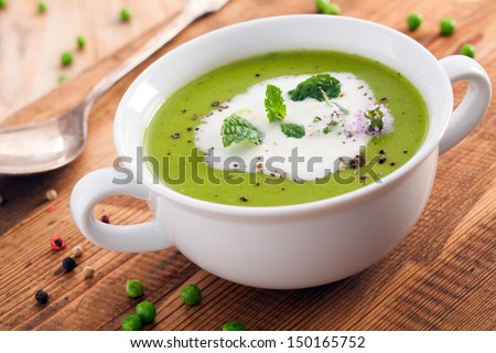 Bowl of healthy green pea soup topped with cream and fresh herbs served as a starter