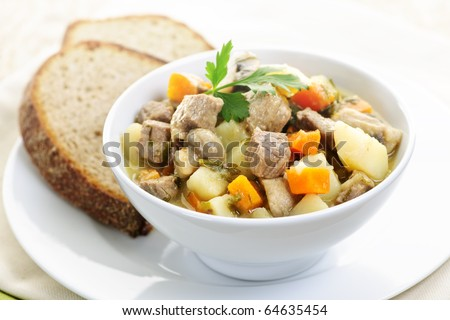 Bowl of hearty beef stew with vegetables served with rye bread
