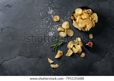Bowl of home made potato chips served with mustard, rosemary, fleur de sel salt on stone background. Top view. Copy space