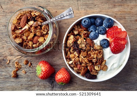 Bowl of homemade granola with yogurt and fresh berries on wooden background from top view Stockfoto ©