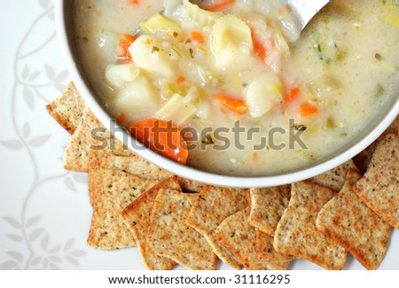 Bowl of homemade potato soup with crackers on decorative serving plate.  Macro with shallow dof.  Focus on vegetables in spoon.