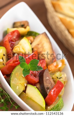 Bowl of homemade Ratatouille made of eggplant, zucchini, bell pepper and tomato and seasoned with herbs (garlic, thyme, oregano) with baguette (Selective Focus,Focus on the oregano leaves on the meal)