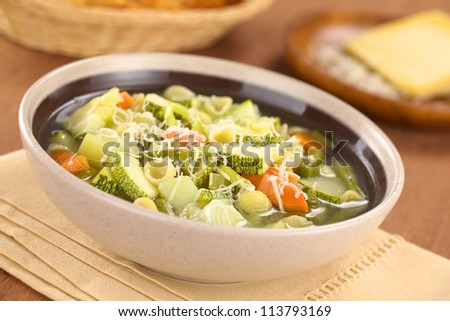 Bowl of homemade vegetarian Italian minestrone soup made of green beans, zucchini, carrots, potatoes, leek and shell pasta with grated cheese on top (Selective Focus, Focus one third into the soup)