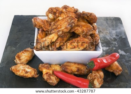 Bowl of hot chicken wings with red peppers