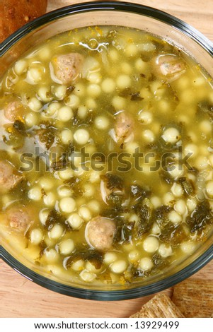 Bowl of hot Italian Wedding Soup (meatballs and spinach soup) in kitchen or restaurant.