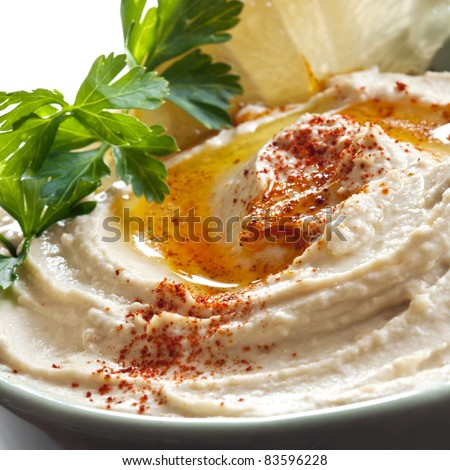 Bowl of hummus topped with paprika.  Traditional chickpea dip.