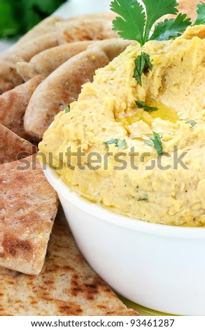 Bowl of hummus topped with pure olive oil and cilantro and served with wedges of pita bread for a healthy snack.  Shallow depth of field.
