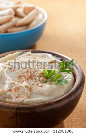 bowl of hummus with parsley and bread sticks