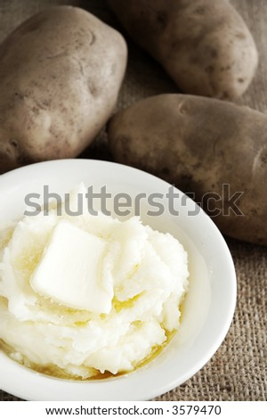bowl of mashed potatoes with butter and whole potatoes