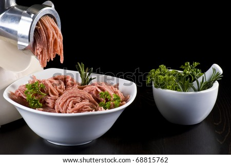 Bowl of mince with electric meat grinder, mortar and pestle