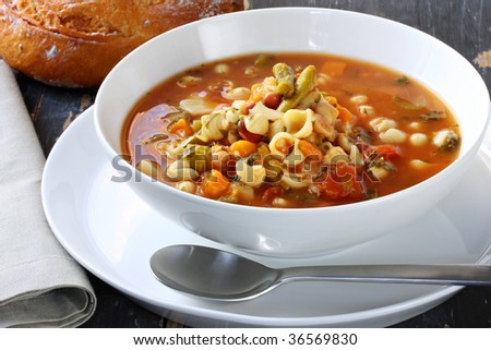 Bowl of minestrone pasta soup, on rustic table, with cob of tomato bread.