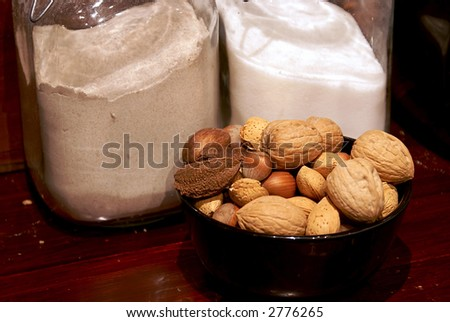 bowl of mixed nuts with sugar and flour containers in the background on wood counter in country kitchen