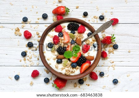 bowl of oat granola with yogurt, fresh raspberries, blueberries, strawberries, blackberries and nuts with spoon on white wooden board for healthy breakfast, top view