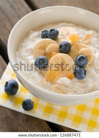 Bowl of oatmeal porridge with bananas and blueberry, selective focus