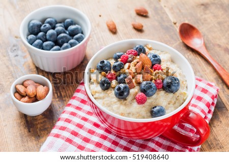Bowl of oatmeal porridge with fresh blueberries, raspberries, almonds and muesli on red plaid textile. Close up. Healthy food, healthy breakfast, healthy lifestyle concept