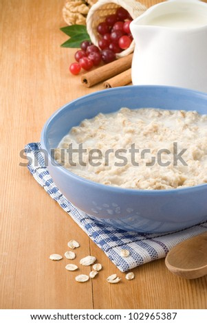 Bowl of oatmeal with berry and milk on wood