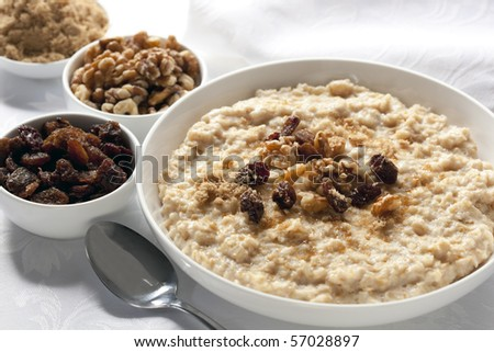 Bowl of oatmeal with raisins, walnuts, and brown sugar.