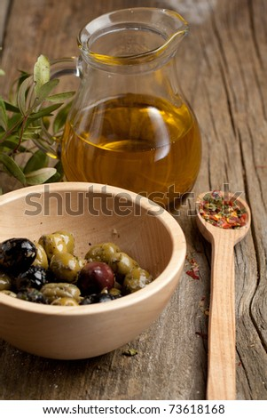 Bowl of olives with jug of olive oil and spoon of spices on old wooden table