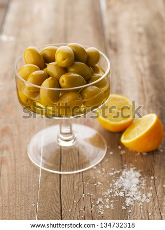 Bowl of olives with lemon and salt on wooden table. Shallow Focus, vibrant color.