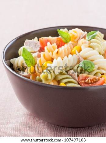 bowl of pasta salad with tuna, tomatoes, sweet corn and basil