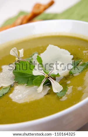 Bowl of pea soup garnished with rocket / arugula leaves and flowers, and shaved Parmesan cheese. Cheese sticks in background. - stock photo