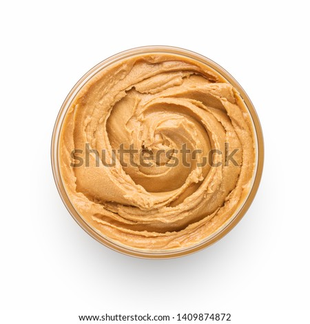 Bowl of peanut butter isolated on white background, top view