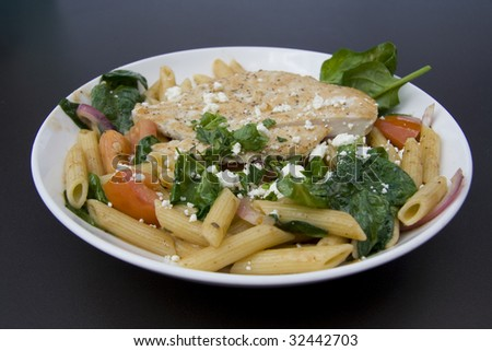 Bowl of Penne pasta with grilled chicken, tomatoes, spinach and feta cheese.