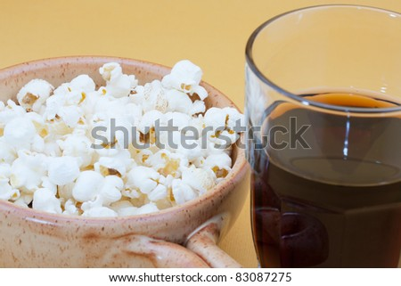 bowl of pop corn and cola
