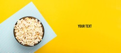 Bowl of popcorn on yellow blue pastel background with copy space. Leisure and entertainment concept. Top view