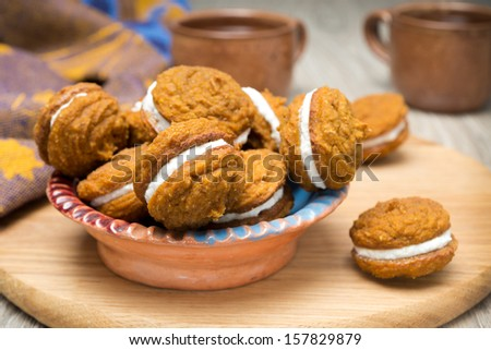bowl of pumpkin cookies with cream filling on a wooden board, horizontal