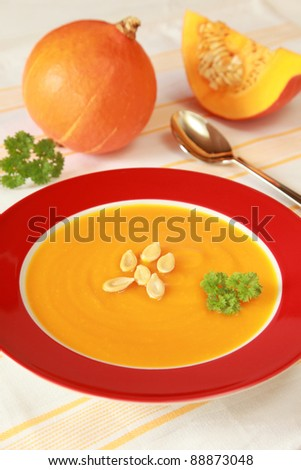 Bowl of pumpkin soup and pumpkins in the background