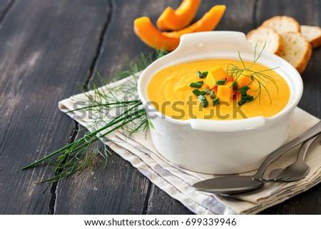Bowl of pumpkin soup on rustic wooden background. Selective focus