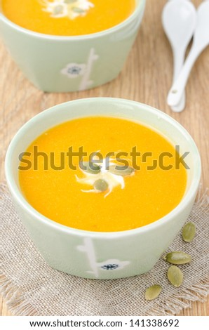 bowl of pumpkin soup with ginger, yogurt and pumpkin seeds, top view