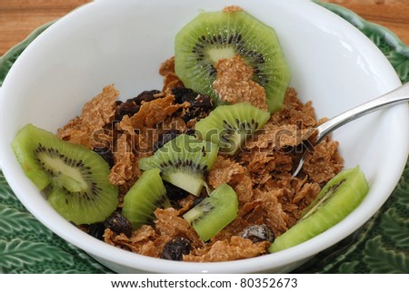 Bowl of Raisin Bran with sliced Kiwi Fruit in white bowl on green plate.
