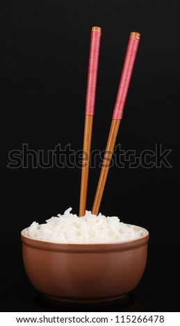 Bowl of rice and chopsticks isoalted on black