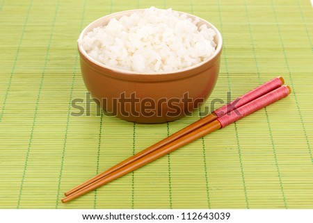 Bowl of rice and chopsticks on bamboo mat