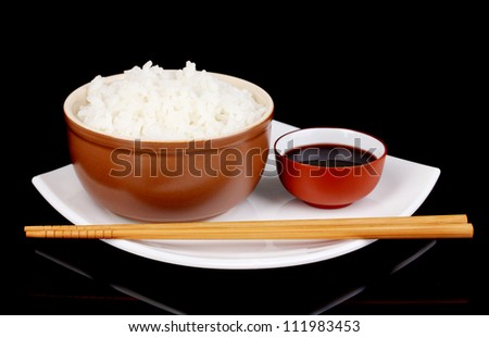 Bowl of rice and chopsticks on plate on grey background - stock photo