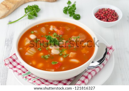bowl of roasted tomato soup with beans, celery and bell pepper, top view, closeup