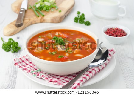 Bowl of roasted tomato soup with beans, celery and sweet pepper. Board with chopped greens, pink pepper and sour cream in the background