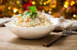 bowl of russian salad olivier with meat and vegetables on a wooden table