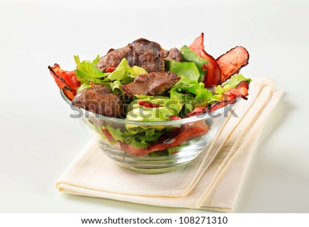 Bowl of salad with chicken liver and thin slices of bacon