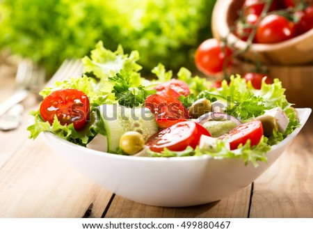 bowl of salad with vegetables and greens on wooden table #499880467